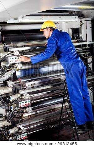 modern printing machine operator checking machine
