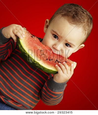 portrait of a handsome kid holding a watermelon and sucking over red background