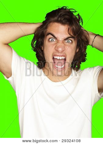 young angry man shouting against a removable chroma key background