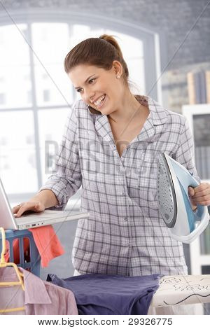 Laughing modern woman multitasking at home, using computer and cellphone, ironing clothes.?