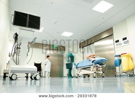 Blurred figures with medical uniforms moving patient in hospital corridor