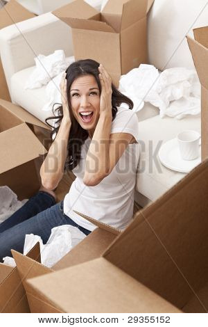 A beautiful single young woman screaming with stress while unpacking boxes and moving into a new home.