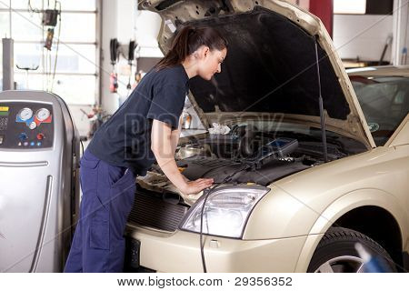 A woman mechanic tuning a car with diagnostic equipment