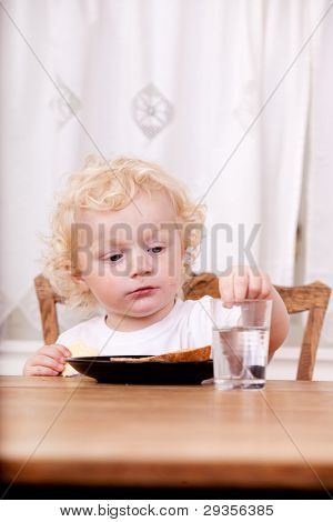 A young child sitting a a table reaching for glass of water