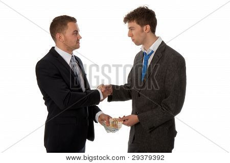 Businessman Shaking Hands. The Deal Is Made And One Businessman Is Paying The Other.