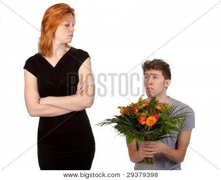 Rapaz oferecendo um ramo de flores para sua namorada com raiva
