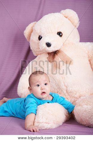 lovely baby boy and a big teddy bear.