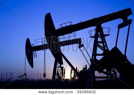 Silhouette of oil pump jacks with sunrise.