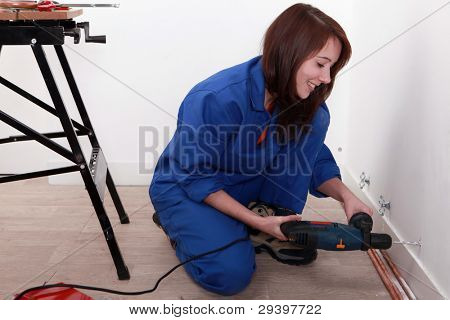 Female labourer drilling hole in wall