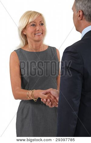 Senior business couple shaking hands