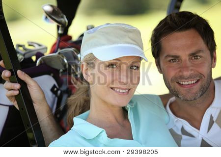 Couple in golf sportswear with clubs in background