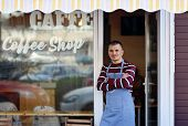 A Handsome Young Coffee Shop Owner Standing In The Entrance Of His Shop. Coffee Shop Inscription On  poster