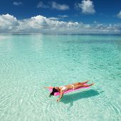 Woman swim and relax in the sea. Happy island lifestyle. White sand, crystal-blue sea of tropical be poster