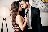 Attractive Girl In Black Dress Holding Tie Of Passionate Man Standing In Suit poster
