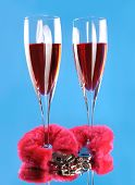 Two wine glasses and pink furry handcuffs conceptual still life isolated on blue background poster