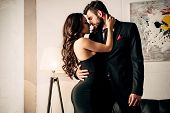Attractive Woman In Black Dress Hugging With Passionate Man In Suit poster
