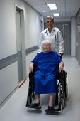 Portrait of a mature Caucasian female doctor pushing a senior Caucasian female patient sitting in a  poster