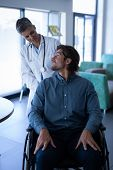 Front view of Caucasian female doctor talking with disabled Caucasian patient in wheelchair in clini poster