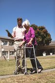 Side view of a Confident Caucasian doctor helping senior Caucasian woman with her walker at backyard poster