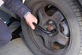 Driver Is Screwing And Unscrewing Changing Car Wheel By Wrench. Damaged Car Tyre. Change A Flat Car  poster