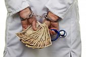 stock photo of deportation  - a doctor with japanese yen bank notes and handcuffs - JPG