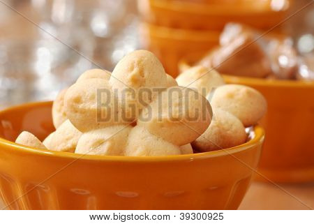Freshly baked sugar cookies (spritz cookies made with cookie press) in gold dessert dish with caramel candies in background.  Macro with extremely shallow dof.