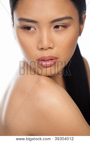 Cropped head and shoulders portrait of a sexy Asian woman with a sultry look and naked shoulders