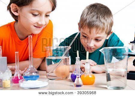 Dois meninos fazendo pesquisas de Bioquímica no laboratório. Isolado no branco