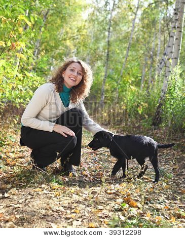 Young Woman Playing With Black Labrador Retriever Puppy