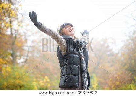 Sorgenlos Frau mit Outstreched Armen im Herbst