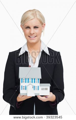Smiling real estate agent holding a model house against white background