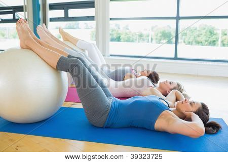 Women doing sit ups with exercise ball in fitnes studio