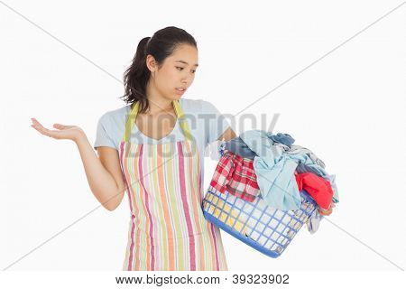 Quizzical looking young woman in apron looking at basket full of dirty laundry