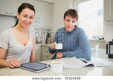 Smiling woman with tablet pc and man with newspaper drinking coffee in kitchen