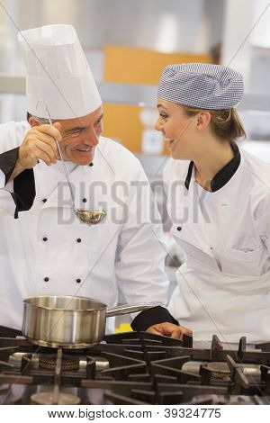 Smiling student and teacher discussing the soup in the kitchen