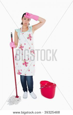 Discouraged woman cleaning the floor with mop and bucket