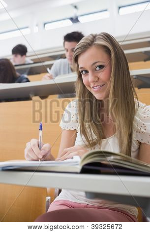 Woman sitting at the lecture hall holding a pen while smiling