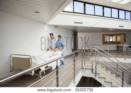 Doctor and nurse pushing patient in bed in the hallway