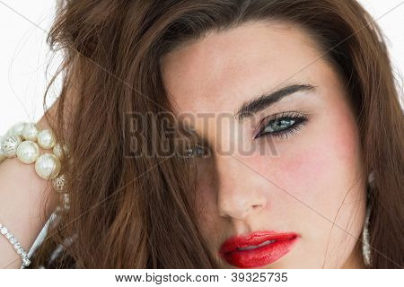 Woman with red lips wearing jewellery while looking at camera