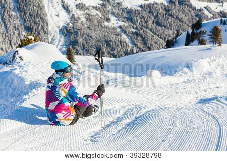 Man sitting on top of Alps, resting after skiing