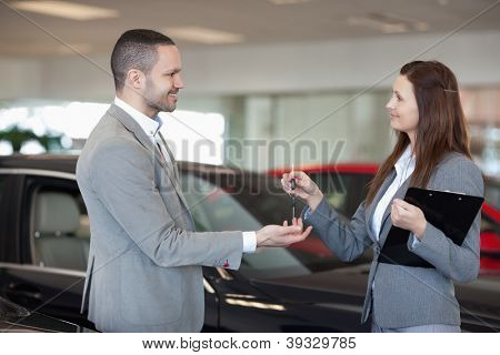 Woman giving car keys to a client in a dealership