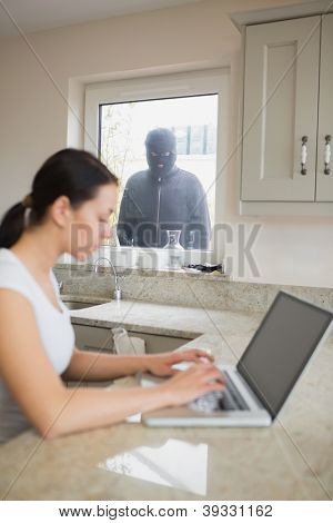 Young woman using her laptop and is observed by a robber at the window