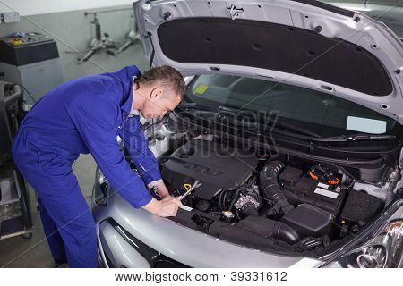 Concentrated mechanic repairing a car in a garage