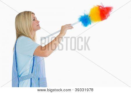 Señora de la limpieza con un plumero en el fondo blanco