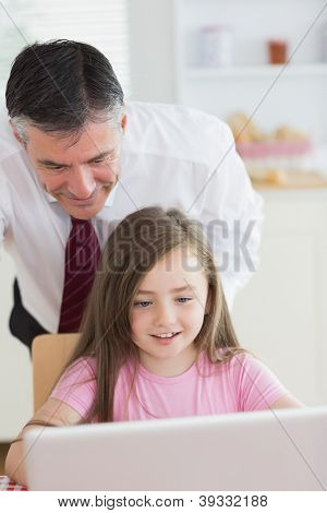 Father standing and child sitting looking at the laptop before work