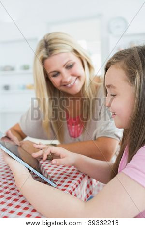 Mother and little girl using a tablet pc while smiling in the kitchen