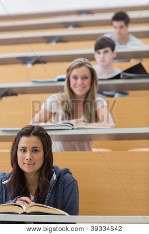 Students sitting looking and smiling at the lecture hall