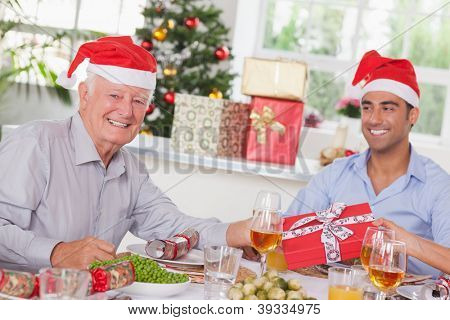 Family swapping christmas presents at christmas dinner