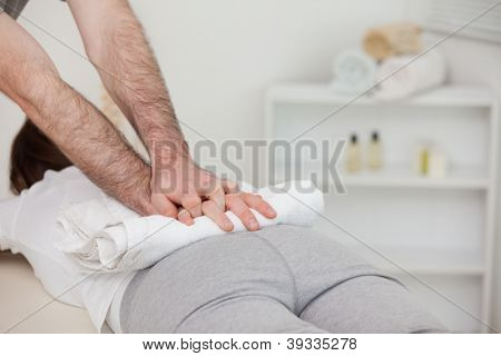Masseur massaging a woman with a towel in a physio room