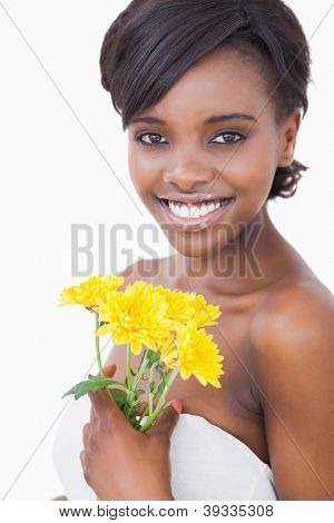 Woman smiling while holding yellow flowers on white background